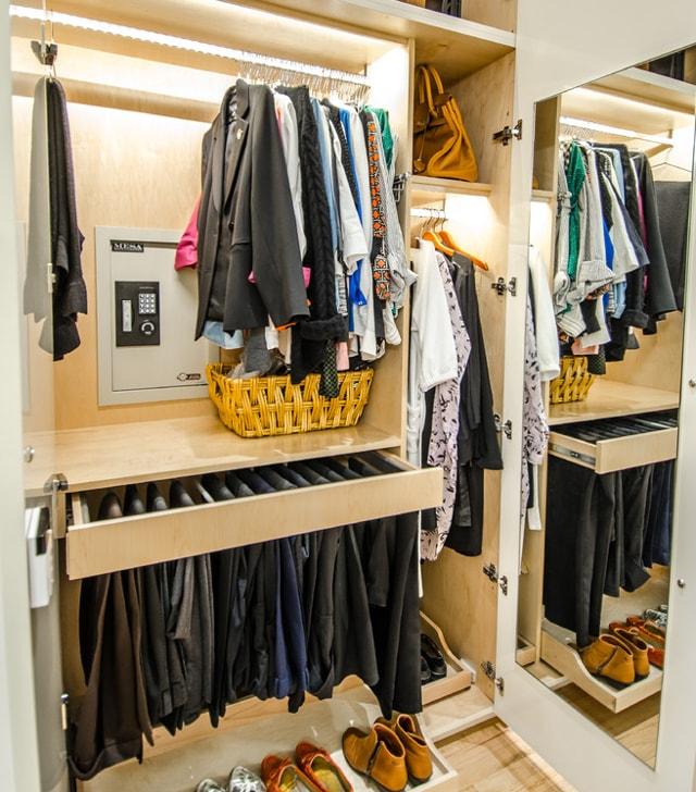 Встраиваемый сейф в гардеробной, спрятанный в закрытом шкафу за одеждой.